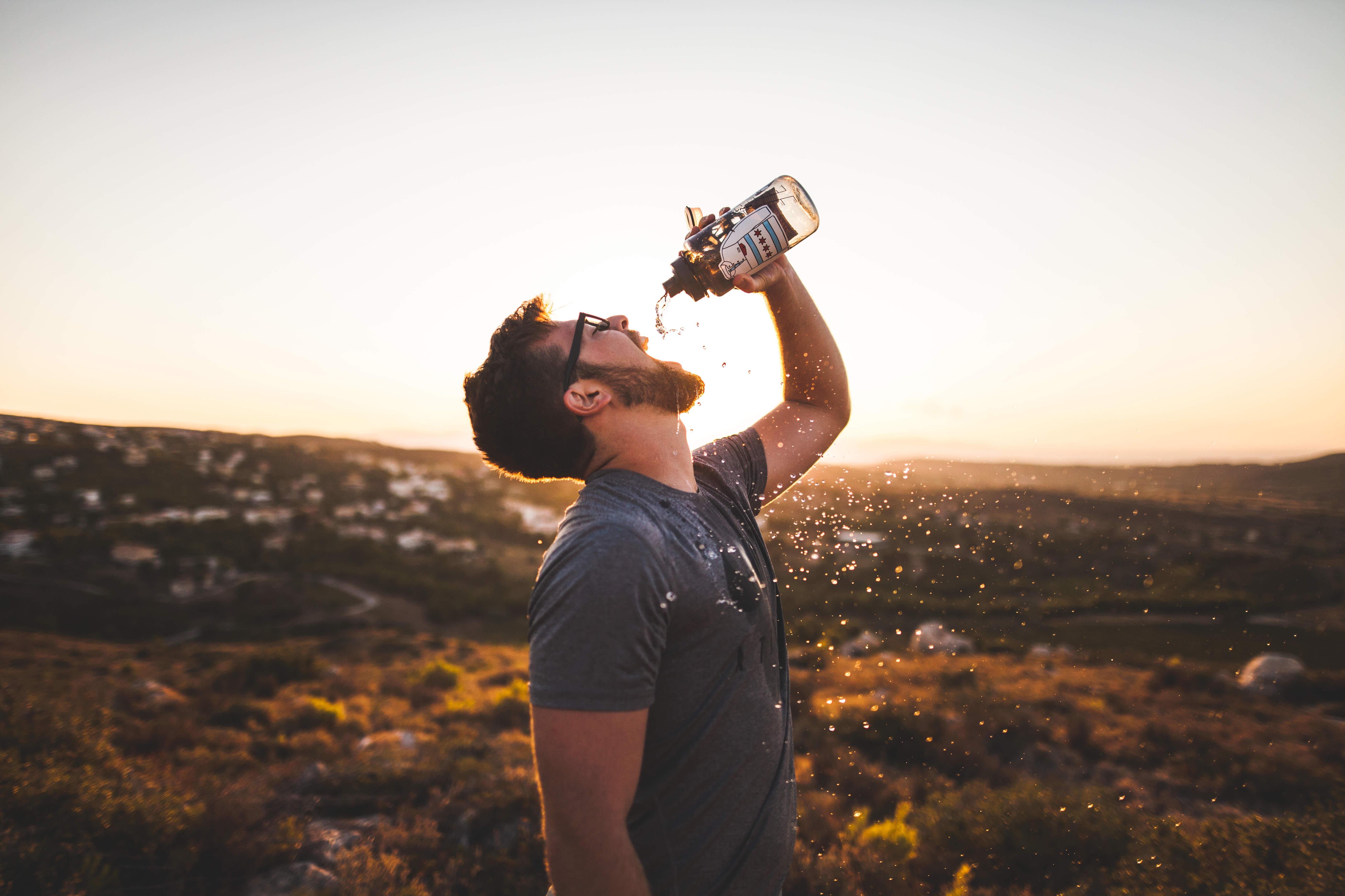 jeune homme buvant de l'eau par temps chaud